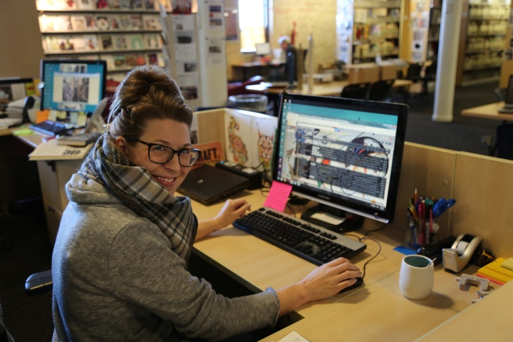 Person smiling while working at a computer station within a library