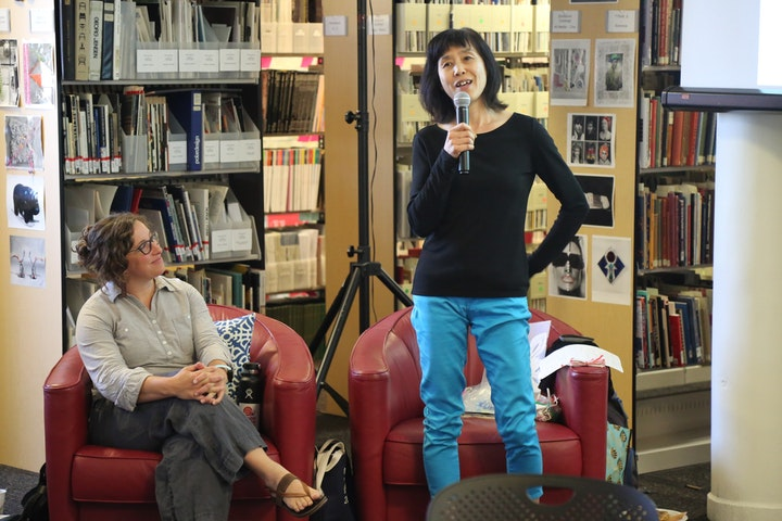 Person with microphone talking to a group of library visitors
