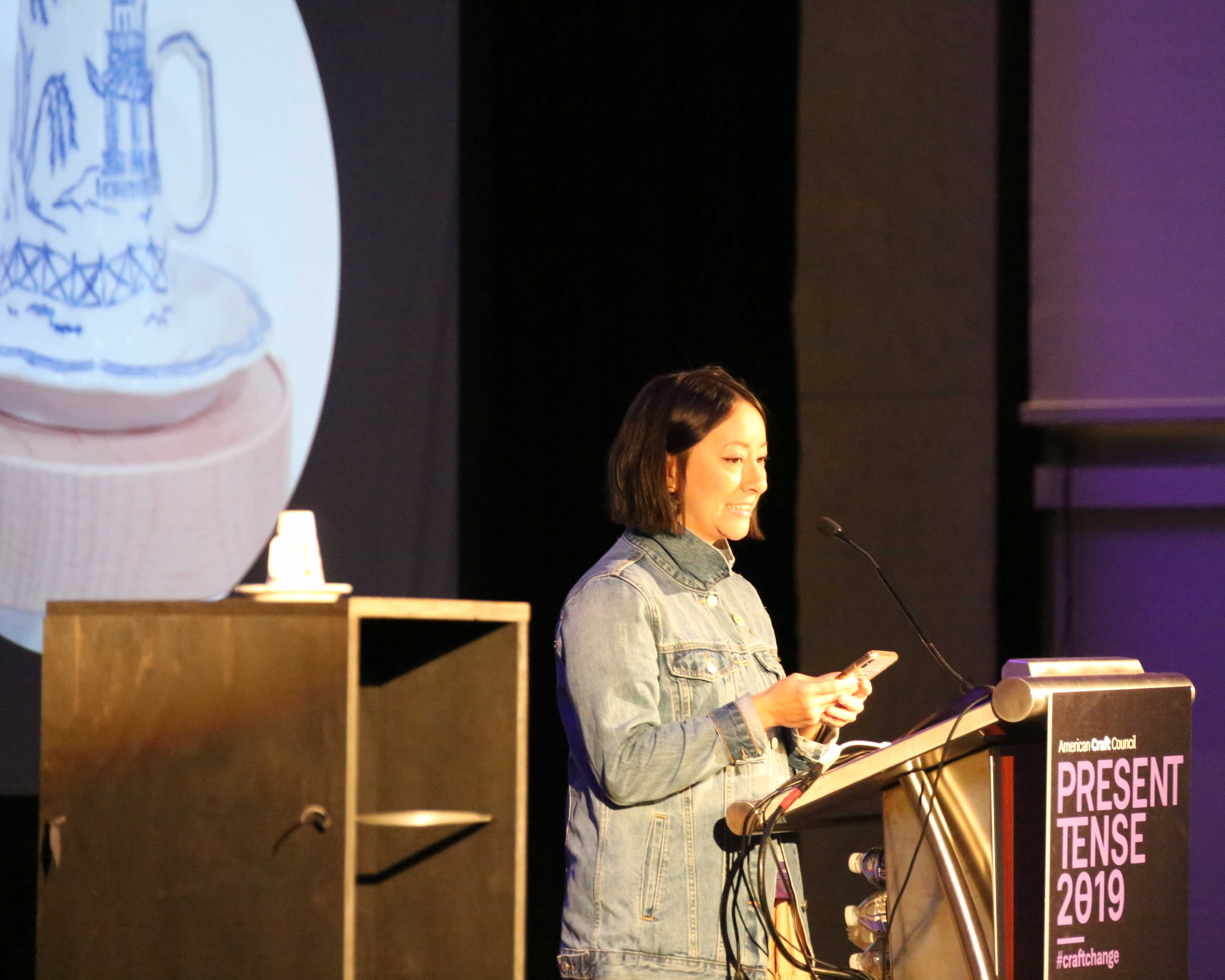 Person presenting at a podium beside a ceramic cup on a pedestal with slideshow image in backdrop