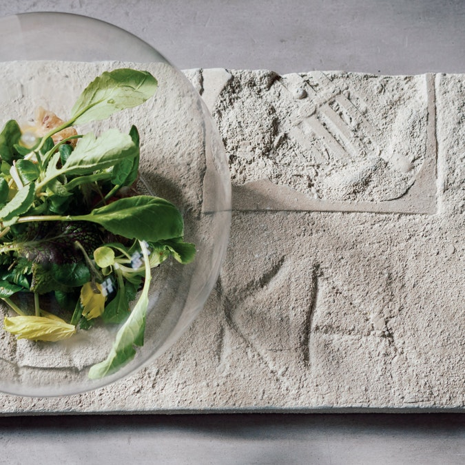 salad inside of a glass orb on a cement platter with carved letters and impressions
