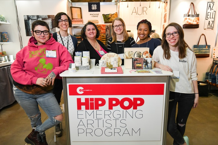 Group of artists posing together in a shared booth space at a craft show
