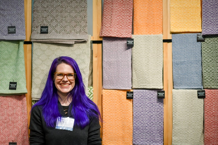 Person with long purple hair smiling in front of wall of handmade linens