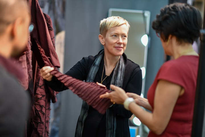 Wearables artists holding out maroon fabric to customer at craft show booth