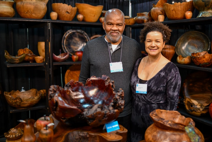 Couple of artists posing amid their assorted handmade bowls in their craft show booth
