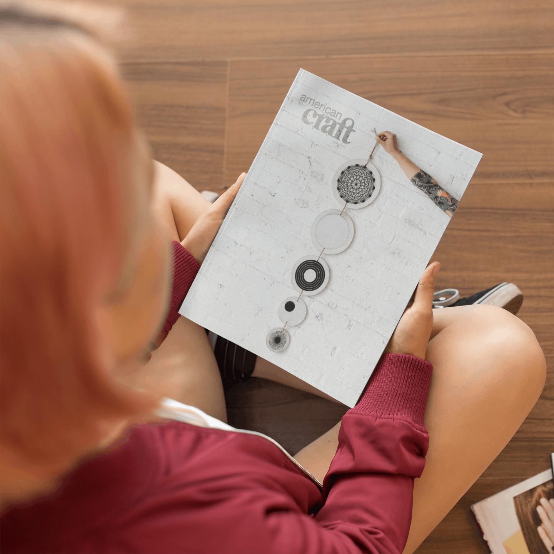 Girl sitting on wood floor holding copy of American Craft magazine